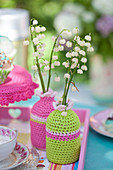 Lily-of-the-valley in vases with crocheted covers in light green and pink
