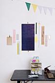 Collage aus Papier an der Wand überm Schreibtisch