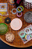 Masking tape and craft materials in a wicker tray