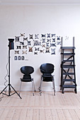 Black designer chairs, studio lights and a ladder in front of a picture wall