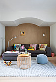 Grey sofa with colourful scatter cushions against brown wall and drum-shaped coffee table in living room