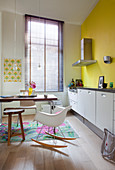 Classic rocking chair, table and white base units in kitchen with yellow wall and louvre blind on window