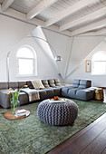Sofa set in living room of attic apartment with white-painted wooden ceiling