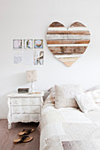 Romantic scatter cushions on double bed, bedside cabinet and love-heart decoration on wall of bedroom
