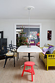 Eclectic dining room with a yellow kitchen bench and a view of the living room