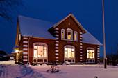 Beleuchtetes Backsteinhaus im Schnee
