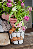 Bouquet of tulips, shepherd's purse and Australian waxflowers in wire basket with eggs