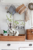 Jug of twigs on wooden tray with vintage flea-market accessories