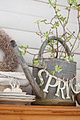Garland of paper letters spelling 'Spring' on metal watering can of twigs