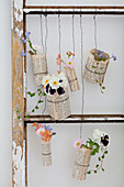 Flowers in glasses covered in book pages and hung in old window frame