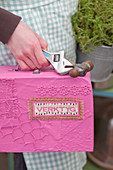 Hand trägt selbstgemachten Werkzeugkoffer in Pink