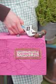 Pink, handmade tool box being carried