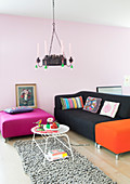 Sofa and brightly coloured ottomans in living room with pale pink wall