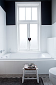 Bathtub below window in black-and-white bathroom