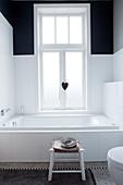 Bathtub below window in black-and-white bathroom