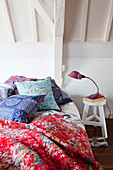 Colourful scatter cushions and quilt on bed in white attic room