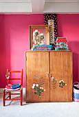 Old wooden wardrobe with floral motifs on doors against hot-pink wall in girl's bedroom