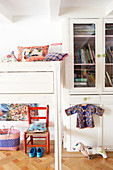Colourful cushions on white loft bed next to glass-fronted cupboard in child's bedroom