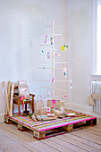Minimalistic Christmas tree made of wooden sticks on a pallet covered with washi tape