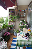 Lush greenery, summery flowers and breakfast tray on balcony