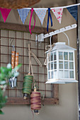 Lantern, twine and gardening tools hung on metal grid and string of bunting