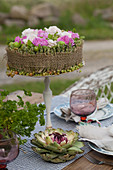 Cake-shaped arrangement of carnations, roses and berries on cake stand
