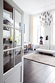 Blick durch geöffnete Tür auf weiße Ledercouch und Schneiderpuppe in Loft-Wohnung