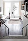 Blick von Treppe auf weiße Ledercouch und Schneiderpuppe in Loft-Wohnung