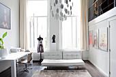 Schreibtisch mit Drehstuhl, weiße Ledercouch und Schneiderpuppe in Loft-Wohnung
