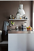 Kitchen counter with stainless steel worktop, overhead pendant lights