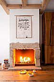 Poster with motto above fire in open fireplace with stone surround