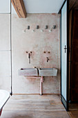 Twin concrete sinks with vintage, wall-mounted tap fittings
