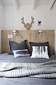 Cushions with feather and cones on the bed with wooden headboard