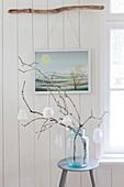 Zweige mit Origami-Anhängern in großer Glasvase, vor Bild mit Landschaftsmotiv am Ast hängend