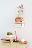 Books and vase on small shelf above candle, books and cactus on table