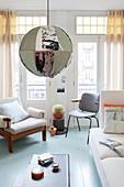 Kugelleuchte mit buntem Stoffschirm, helles Sofa, Stuhl und Sessel im Altbau-Wohnzimmer