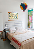 Double bed with metal headboard, poster of bird and spherical lamp with colourful fabric lampshade