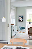 View over dining table into living area with rocking chair and muted colour scheme