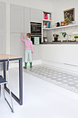 Girl standing in front of grey cupboards in kitchen with pattern painted on floor