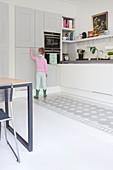 Mädchen am grauen Schrank in der Küche mit bemaltem Boden