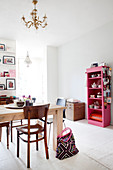 Solid wood table and pink shelf with dishes in the dining area