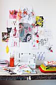 Arbeitstisch mit Nähmaschine, verschiedene bedruckte Stoffe an der Wand