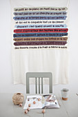 Table with crafting materials, behind it a wall hanging with a message