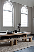 Long wooden table and benches on rug next to arched windows