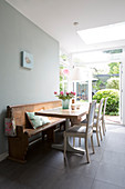Wooden table with white chairs and old wooden bench on grey tiled floor