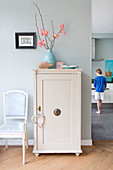 Chair next to old cupboard with accessories in pastel shades and boy in background