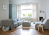Modern grey sofa set in living room with large window and parquet floor