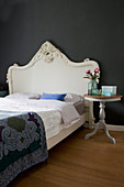 Bed with Baroque headboard and pedestal table against black wall