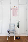 Rosafarbene Bluse hängt am Schrank über hellblauem Stuhl