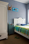 Antique furniture and grey-blue walls in child's bedroom